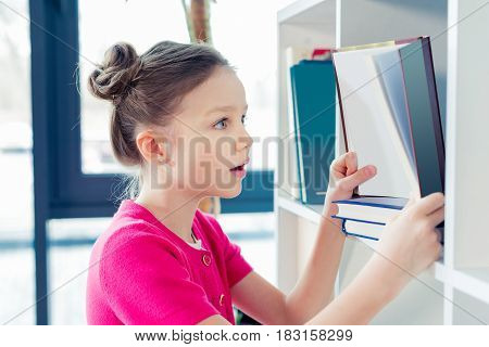 Side View Of Surprised Little Girl Holding Open Book And Looking Inside