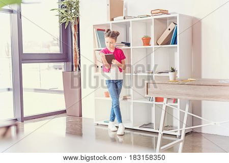 Full Length View Of Focused Little Girl Standing And Reading Book In Office