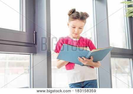 Adorable Smiling Little Girl Standing Near Window And Reading Book