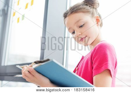 Low Angle View Of Smiling Little Girl Standing Near Window And Reading Book