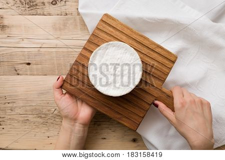 Top view on Camembert cheese on wooden board in woman's hands. Serving French homemade soft cheese. Food concept