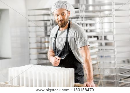 Portrait of a handsome cheese maker in uniform forming cheese into molds at the small producing farm