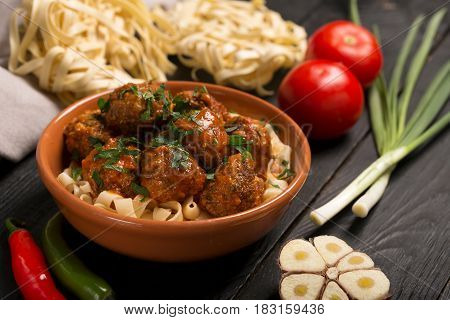 Meat balls with tomato sauce and pasta, close-up. Raw ingredietns on the table. Horizontal orientation