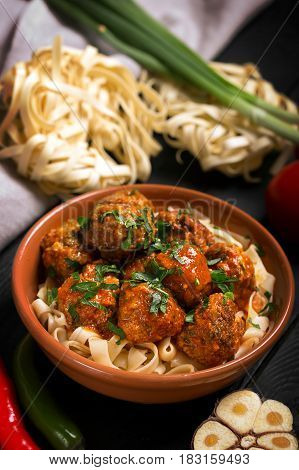 Meat balls with tomato sauce and pasta, close-up. Raw ingredietns on the table