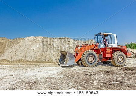 Red loader with wheels at earthmoving works he is pushing sand on huge pile preparing pile of for loading in truck on building site.
