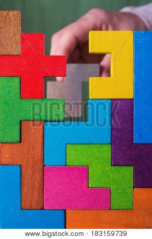 Hand with wooden toy blocks. Businessman builds a tower of wooden multi-colored blocks. Concept of business success cooperation achievement.