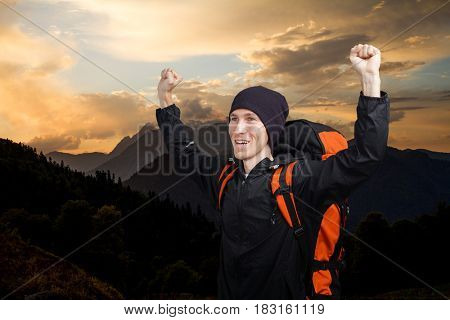 Man hiker with backpack raised her hands up against a mountain sunset landscape.