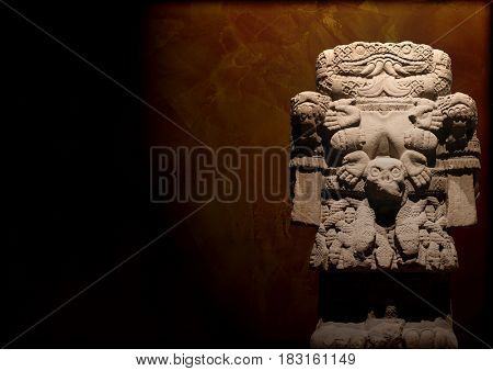Grunge background with Aztec goddess of death Coatlicue (mother of Quetzalcoatl). Statue of woman with a snake's head and stucco texture of brown color. Copy space
