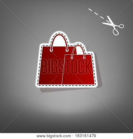 Shopping bags sign. Vector. Red icon with for applique from paper with shadow on gray background with scissors.