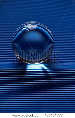 Glass globe or drop of water on a background of blue corrugated paper . Clean and Shine