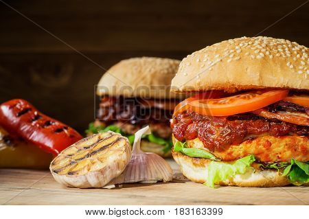 Two fresh tasty burger. Homemade hamburger with fresh vegetables close-up. Sesame buns with succulent beef patty grilled onions bacon tomato and fresh salad served on rustic wooden board.