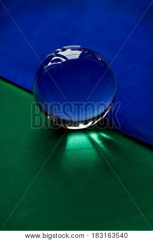 Glass globe or drop of water on a background of green and blue velvet paper. Clean and Shine