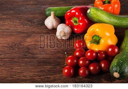 Heap of fresh organic tasty vegetables on brown wood background for menu or recipe. Healthy natural food on wooden table. Bright peppers and other cooking ingredients above view