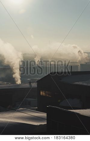 Industrial buildings in the fog on the blue sky backgrond. Warehouses. Smoke from the pipe. Smog.