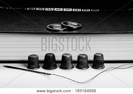 Old Thimbles and a needle and thread on a background of book pages. The buttons on the book. Conceptual photography. Monochrome.