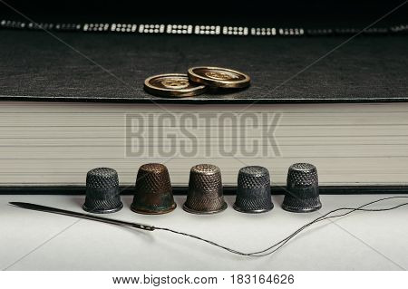 Old Thimbles and a needle and thread on a background of book pages. The buttons on the book. Conceptual photography.