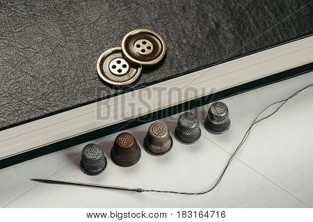 Gold Buttons on the book. Old Thimbles and a needle and thread on a background of book pages. Conceptual photography.