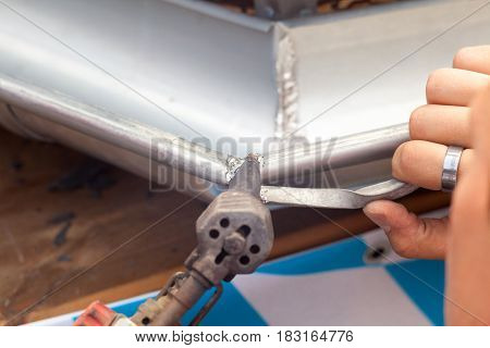 Close-up of a roofer applying weld into the gutter parts to assemble it