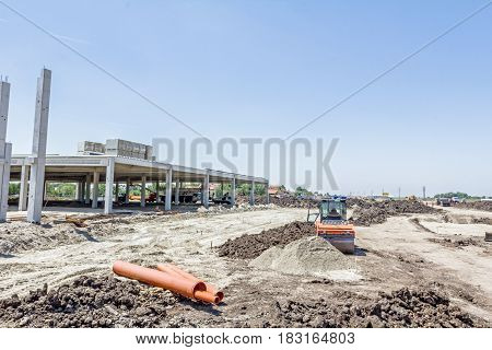 Unfinished concrete edifice road roller is compacting leveling soil at construction site
