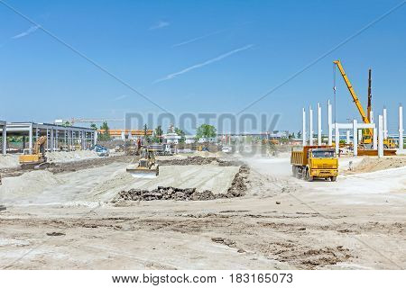 Heavy earthmover construction machine is leveling sand at building site.