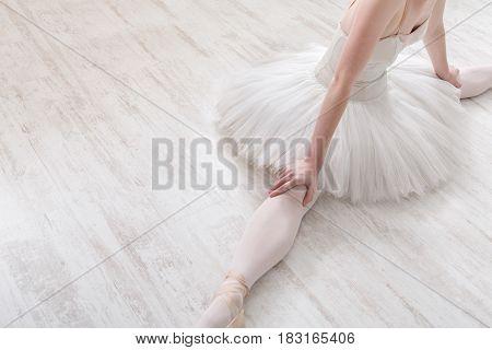 Classical Ballet dancer. Beautiful graceful ballerine in tutu skirt practice split ballet position, top view, unrecognizable, crop.