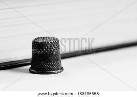 One old thimble against the background of the pages of the book. Monochrome.