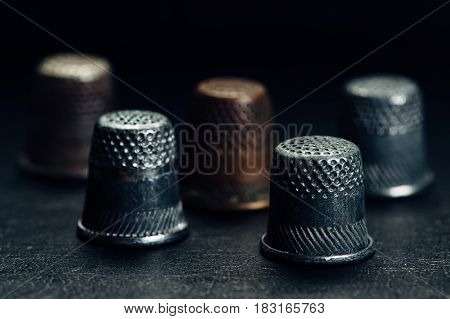 A few old thimbles on a black background.