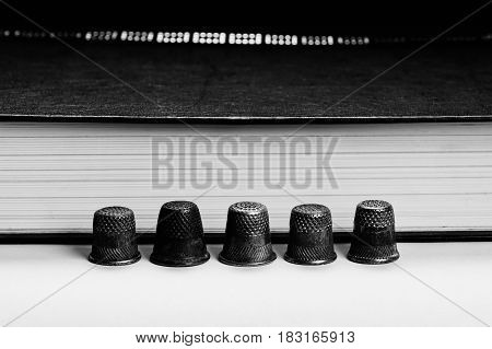 Several old ones in a row of arranged thimbles on the background of the pages of the book. Monochrome.