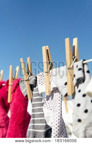 Colorful socks hung out to dry on a washing line in the bright warm sun. Background is a clear blue sky.
