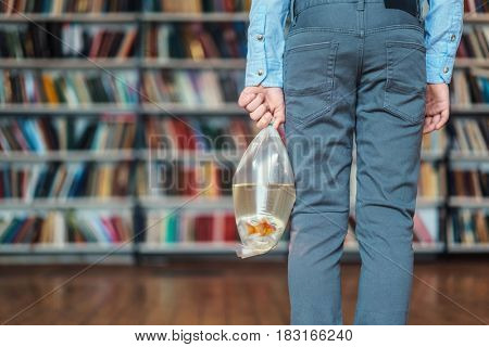 Boy with goldfish in library