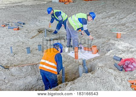 Zrenjanin Vojvodina Serbia - May 30 2015: Construction workers are assembly PVC pipes and place them in trench on building site.