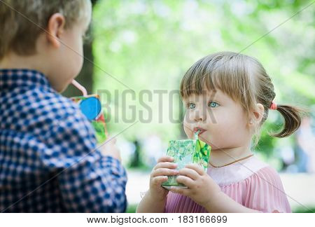 Lovely little girl and boy drinking juice