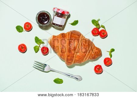 Breakfast with fresh croissants and jam top view