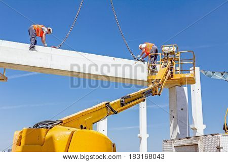 Mobile crane is carry concrete joist to assembly edifice height workers are in cherry picker are placing truss on building skeleton.