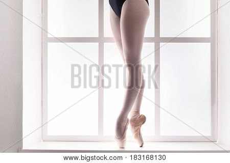 Closeup legs of young ballerina in pointe shoes at window background, high-key. Ballet practice on training. Beautiful slim graceful feet of ballet dancer, unrecognizable female.