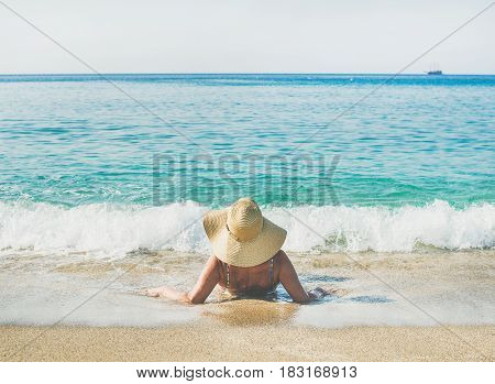 Beautiful slim senior woman tourist in bikini and hat lying on sand enjoying sea at Meditteranean resort of Turkey in Alanya, Kleopatra beach