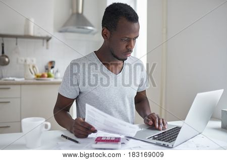 Concentrated young african american student using online banking application with hand on touchpad looking at screen of his laptop trying to make payment for university education. Financial problems