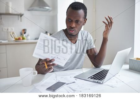Indignant angry irritated african american male sitting at kitchen table looking at papers in shock astonished with amount of unpaid bills. Financial stress feeling depressed and frustrated