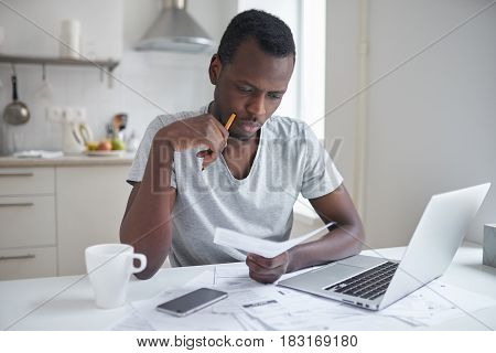 Stressed african american man working through paperwork calculating expenses trying to save some money managing finances sitting at kitchen table with laptop trying to make finance plan