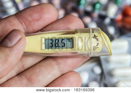 Thermometer in man hand temperature tablets on background of tablets