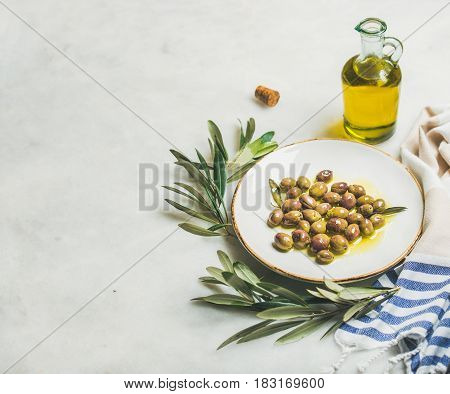 Pickled green Mediterranean olives in virgin olive oil on white ceramic plate, olive tree branch and olive oil in glass jug over grey marble background, selective focus, copy space
