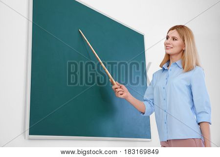 Female teacher with pointer standing near blackboard