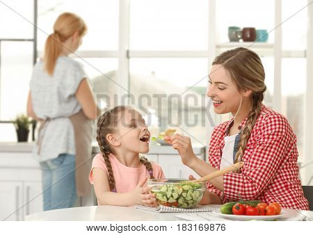 Young woman with her daughter eating salad in kitchen