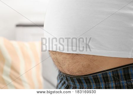 Man with big beer belly at home