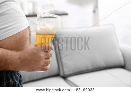Man with big belly holding glass of beer at home