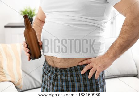 Man with big belly holding bottle of beer at home