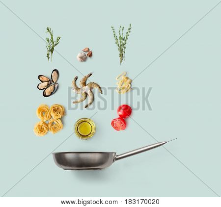 Cooking italian food, seafood pasta, isolated on blue. Frutti di mare with fettuccine spaghetti. Mussels, prawn, shrimp, calamari rings and other ingredients over frying pan