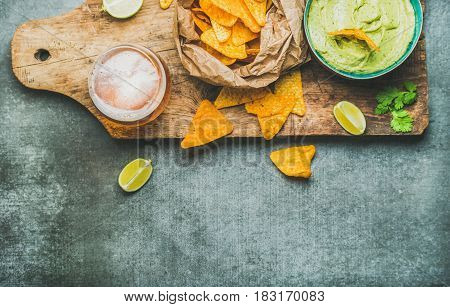 Fresh guacamole sauce in blue ceramic bowl, mexican corn chips, glass of wheat beer on rustic wooden serving board over grey concrete table background, top view, copy space