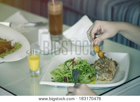 Fish with a salad in a plate is servered on a table with a glass of carrot juice. The female is having lunch.
