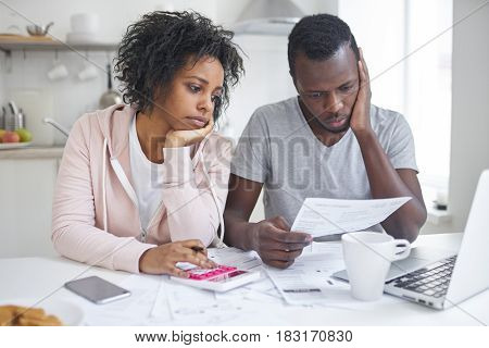 Stressed african american couple looking frustrated having no money to pay off their debts managing family budget together sitting home at kitchen table with lots of papers laptop and calculator